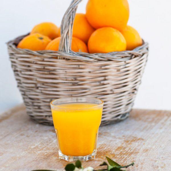 Zumo de naranja y cesta de naranjas